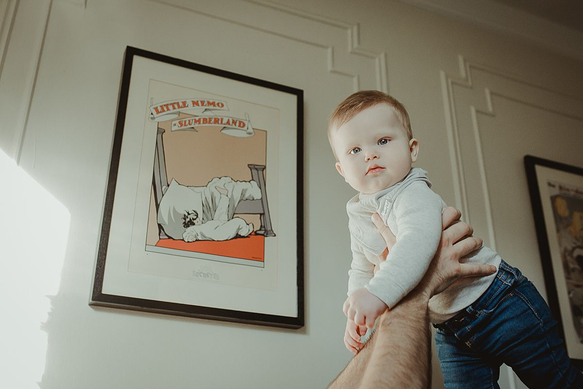 dad holds baby in the air in living room against backdrop of colorful wall hangings. krystil mcdowall photography capturing candid family photos