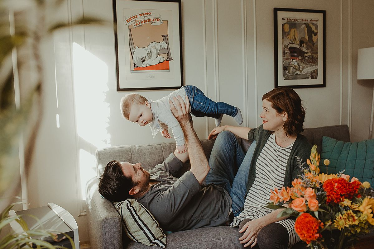 dad holds baby in the air in living room against backdrop of colorful wall hangings while mom sits next to the boys. krystil mcdowall photography capturing candid family photos
