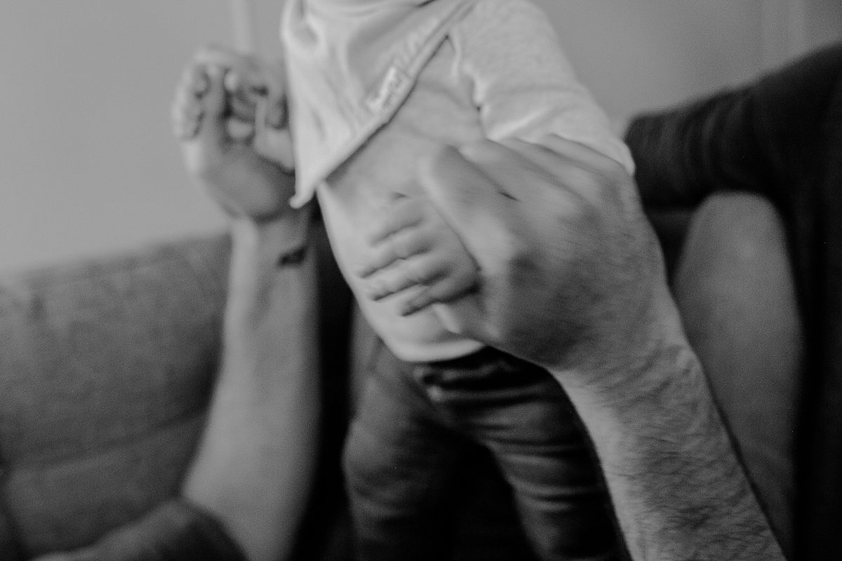 black and white close up photo of dad holding babies hands. photo by nyc family photographer krystil mcdowall