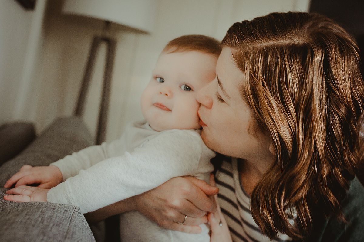 mom holds son while he explores the couch and gives son soft kiss on the cheek. krystil mcdowall photography capturing candid family photos