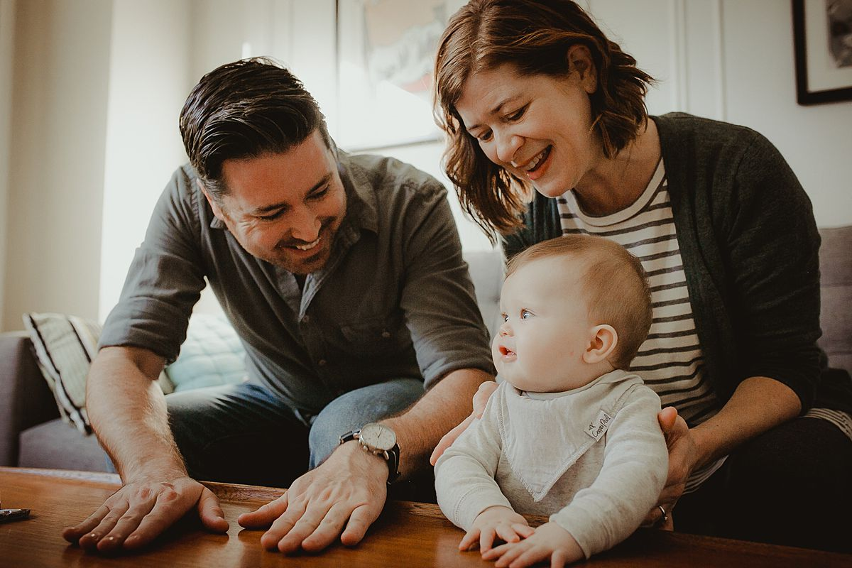 mom, dad and son play in living room together during candid family photo session in queens. krystil mcdowall photography capturing candid family photos