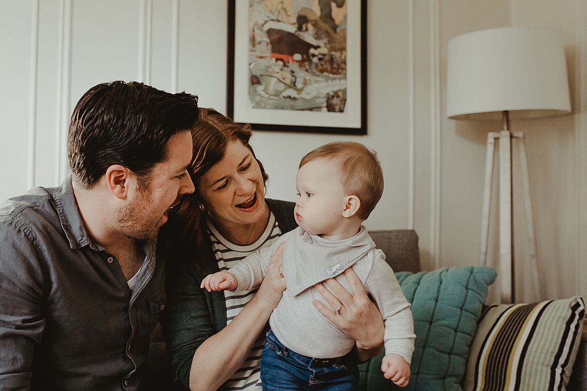 mom, dad and son play in living room together with son sitting on mom's lap during candid family photo session in queens. image by nyc family photographer krystil mcdowall