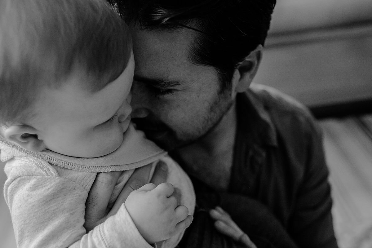 close up photo of dad snuggling into baby son during documentary family photo session with nyc family photographer krystil mcdowall