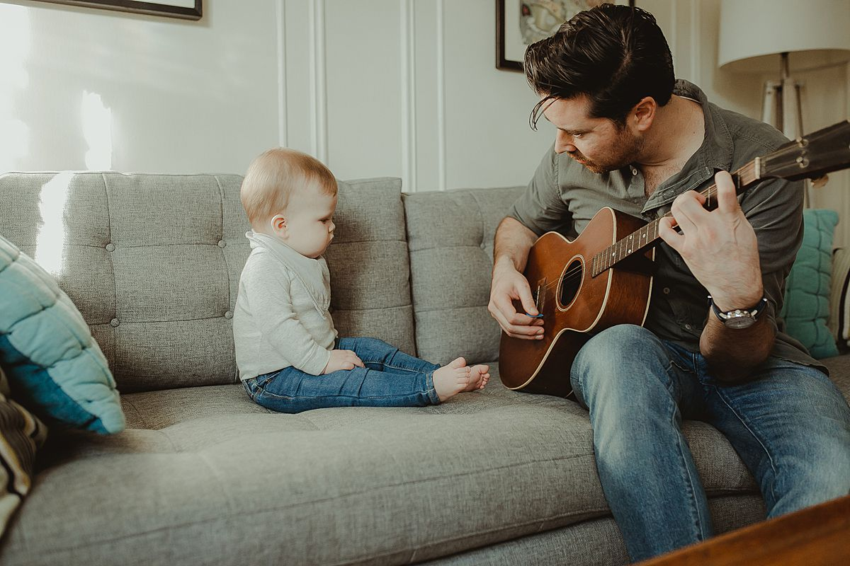dad and son sitting on living room couch while dad plays guitar for his eight month old son during fun family photo session. image by nyc family photographer krystil mcdowall