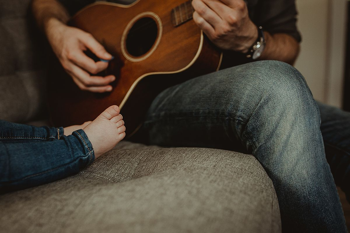 close up details photo of baby feet while dad plays guitar. image by nyc family photographer krystil mcdowall