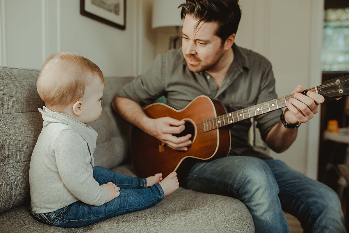 dad and son sitting on living room couch while dad plays guitar for his eight month old son during fun family photo session in queens. image by nyc family photographer krystil mcdowall