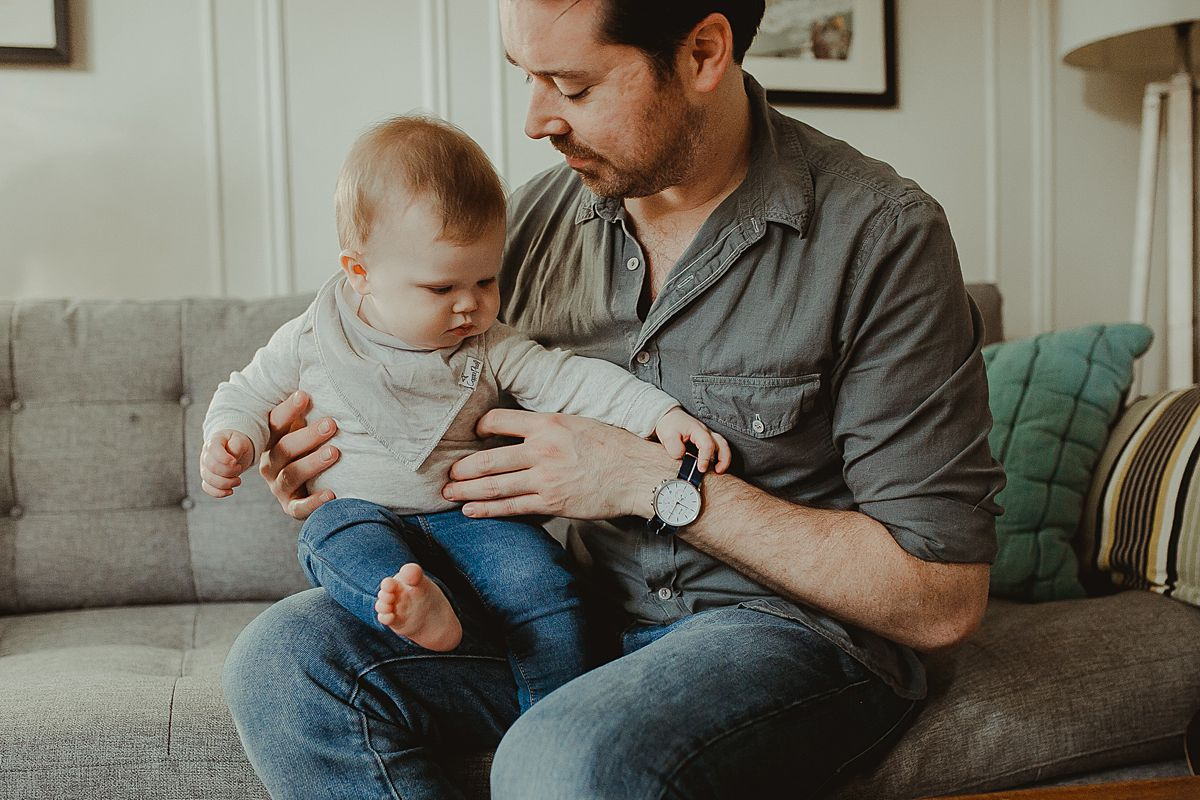 son sits on dad's lap in living room of peaceful queens apartment.mom, baby and dog on sun filled living room couch enjoying listening to dad play guitar during documentary family photo session. image by krystil mcdowall photography