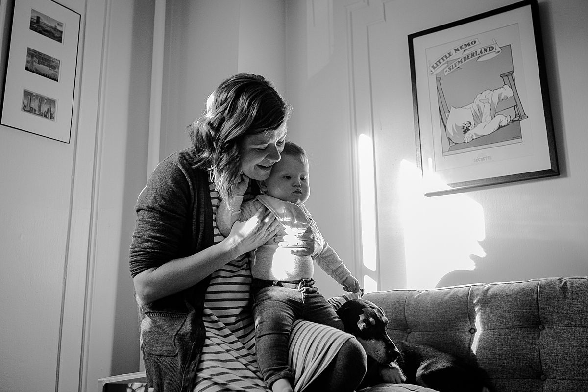 mom, baby and dog on sun filled living room couch enjoying listening to dad play guitar during documentary family photo session. image by krystil mcdowall photography