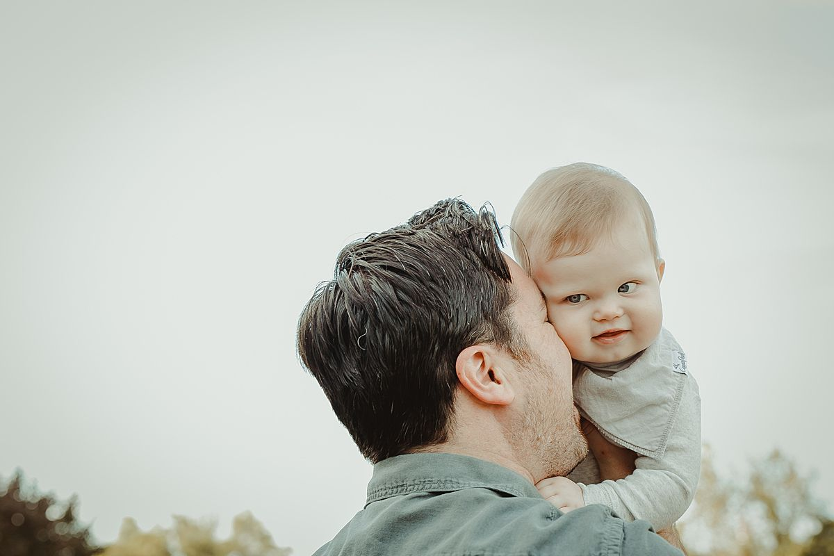 son enjoying cuddles with dad at local park in queens. image by photographer krystil mcdowall