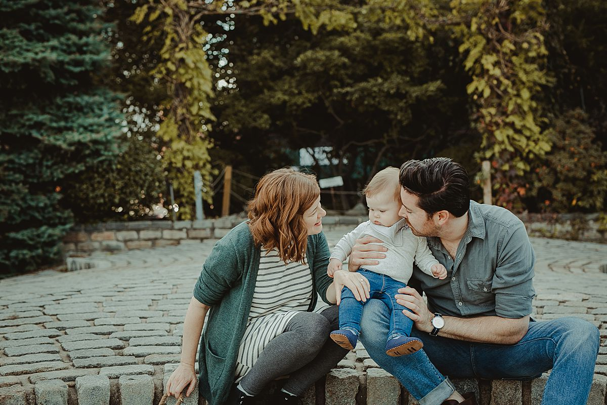 mom, dad and son sitting on step feature at socrates sculpture park in queens.image by nyc family and newborn photographer krystil mcdowall