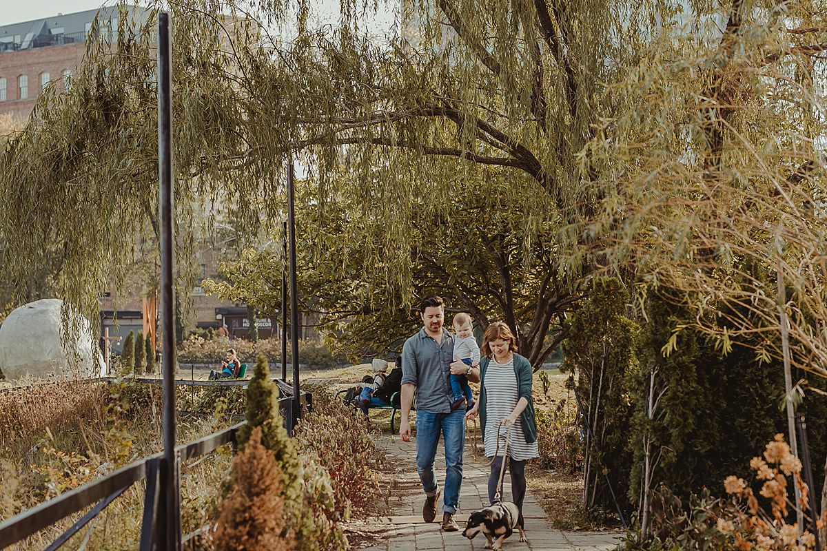 candid photo of family walking their dog at socrates sculpture park. image by nyc family and newborn photographer krystil mcdowall