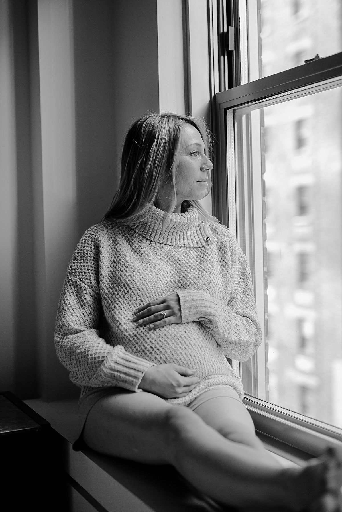 black and white portrait of expecting mom sitting in light filled window of midtown nyc hotel. photographed by krystil mcdowall photography