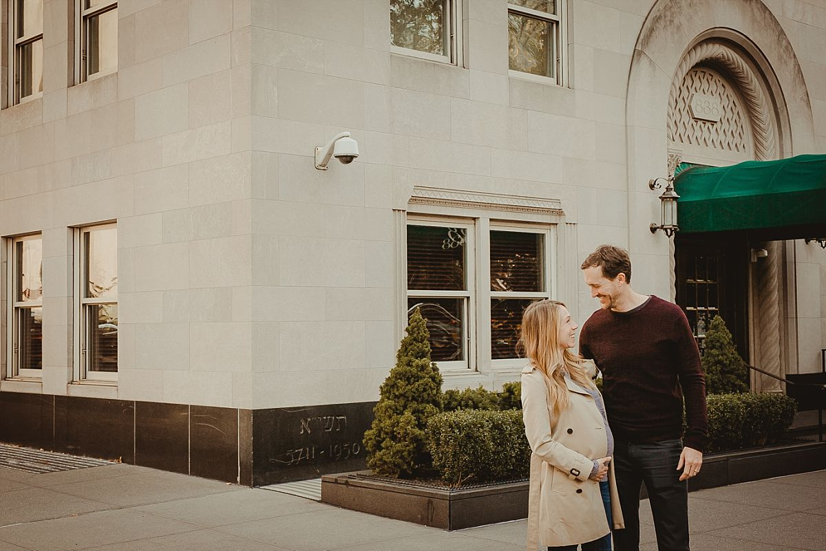 dad and mom pose on 5th avenue during lifestyle family photoshoot. image by nyc newborn and family photographer krystil mcdowall