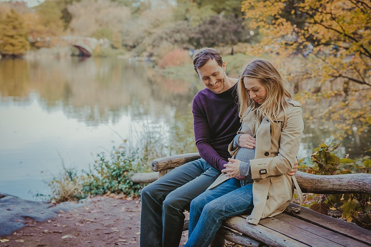 couple sitting in central park in front of gapstow bridge on sunny fall morning. photographed by nyc family and newborn photograher krystil mcdowall