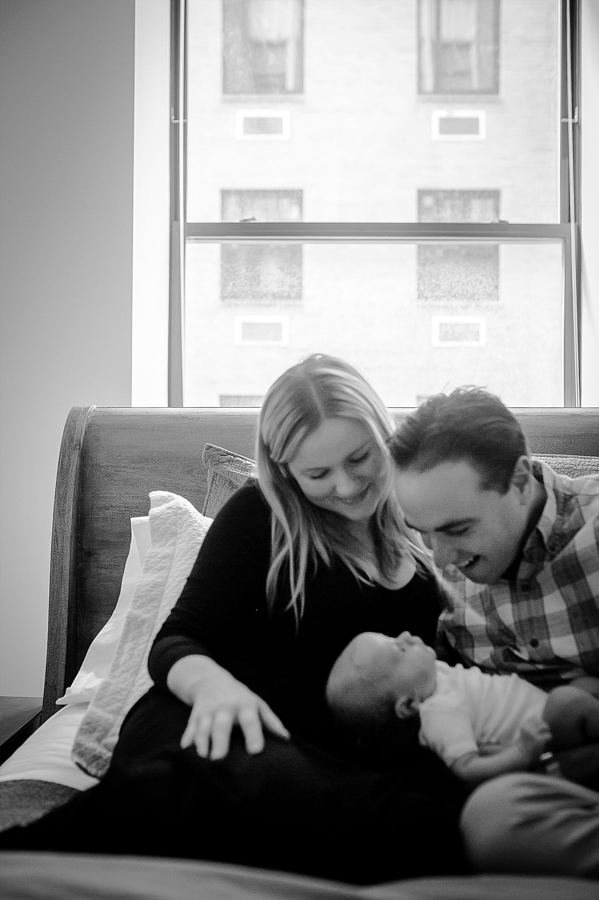 black and white portrait of mom and dad holding newborn daughter while sitting on bed in nyc apartment. image by nyc newborn photographer krystil mcdowall