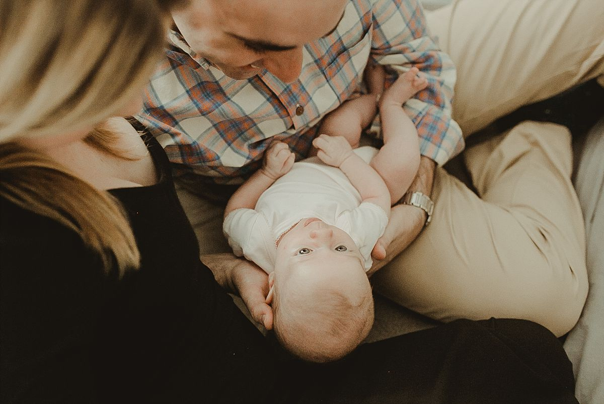 portrait of mom and dad holding newborn daughter while sitting on parents bed in nyc apartment in the fianancial district. image by nyc newborn photographer krystil mcdowall