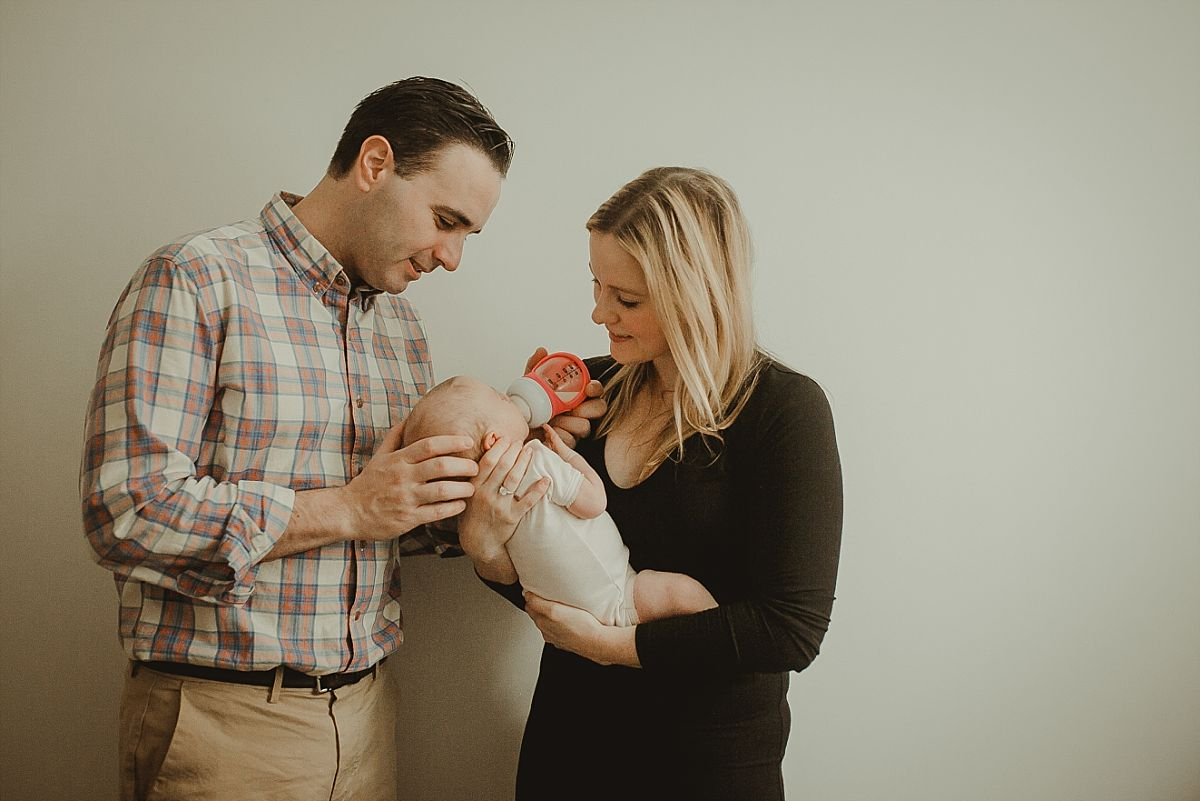 portrait of mom and dad feeding beautiful newborn baby girl in downtown nyc apartment