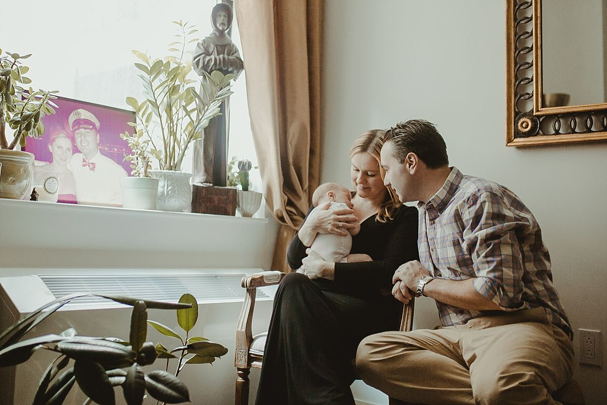 family portrait of mom, dad and newborn daughter as they die in living room of downtown manhattan home. image by nyc newborn photographer krystil mcdowall