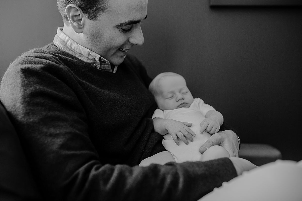 dad holds daughter as she sleeps peacefully in his arms during candid newborn session in downtown new york. photographed by krystil mcdowall photography