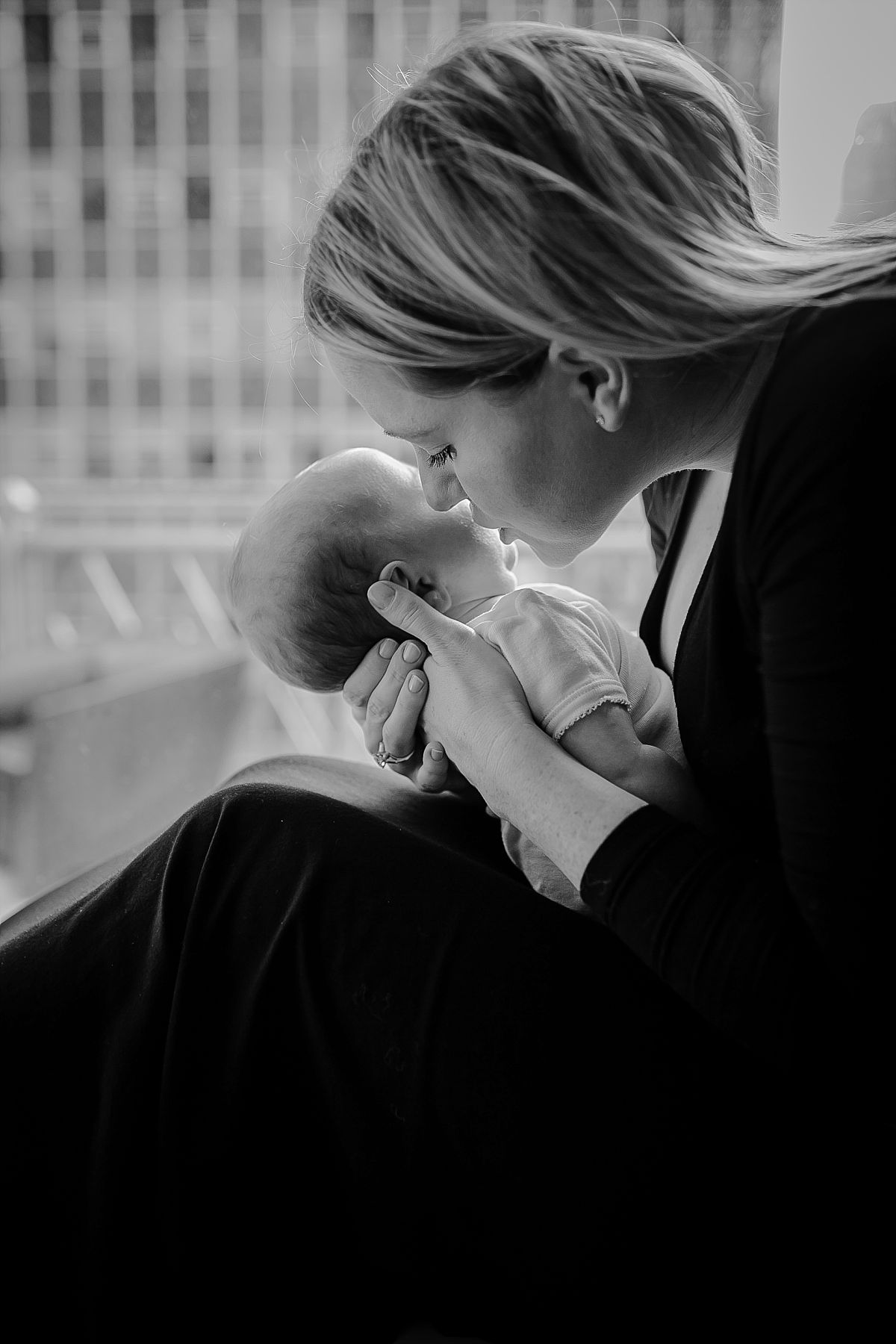 newborn daughter lays on mom's lap and looks up at mom with big eyes. krystil mcdowall photography captures candid family photos