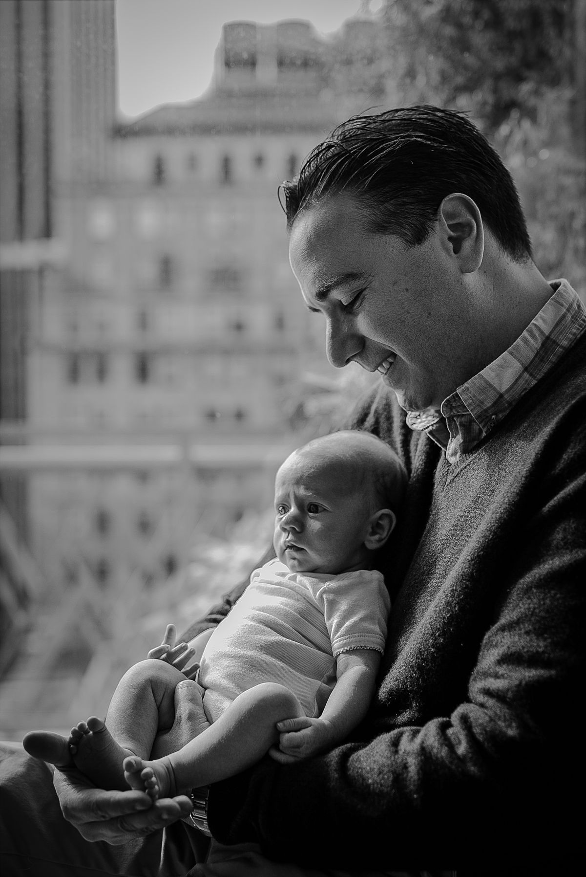 black and white portrait of dad and newborn daughter sitting in window enjoying the sun during newborn session in downtown new york. photo by krystil mcdowall photography
