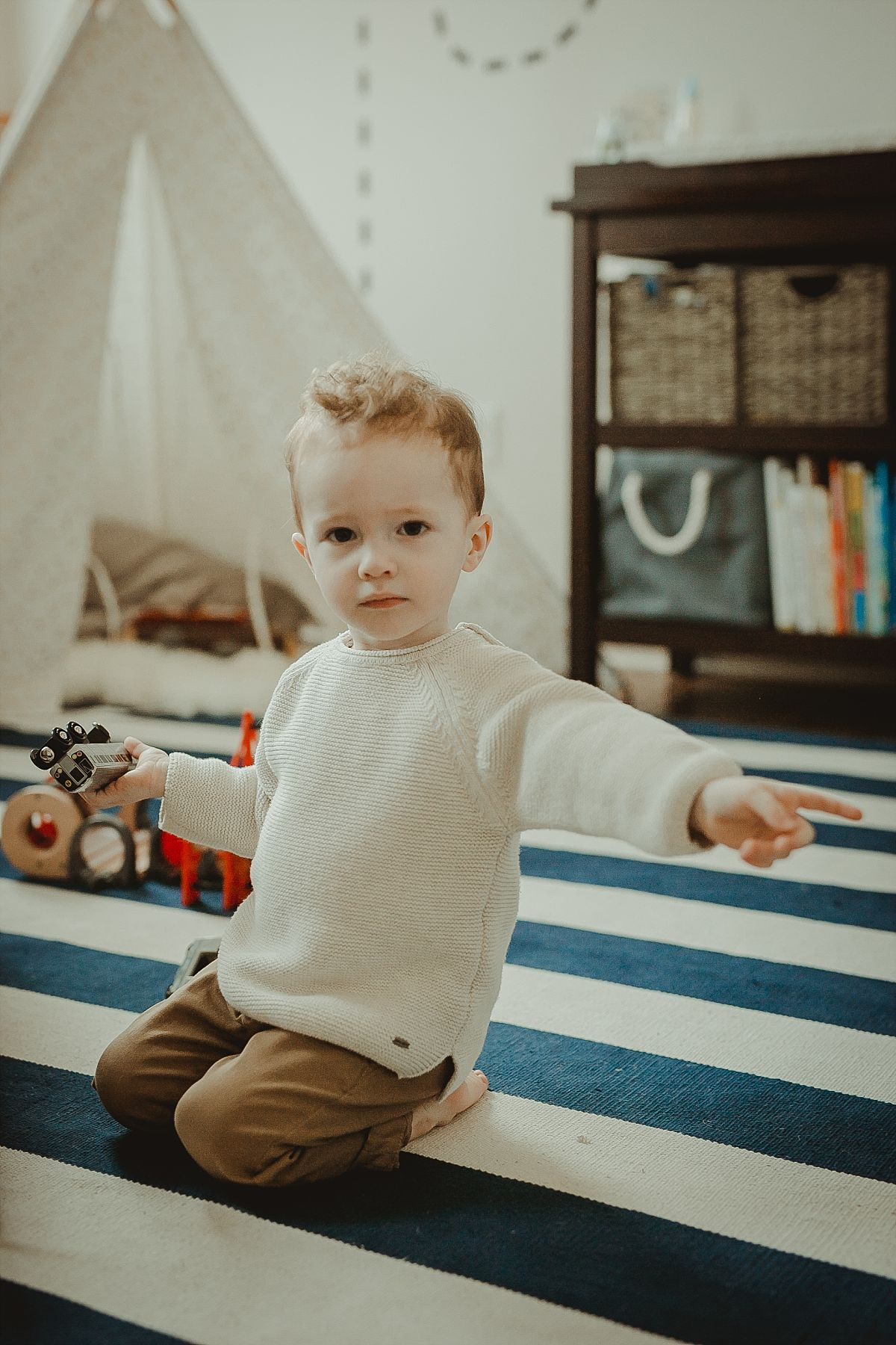 candid portrait of toddler sitting on striped rug and holding a train. photo by nyc family photographer krystil mcdowall