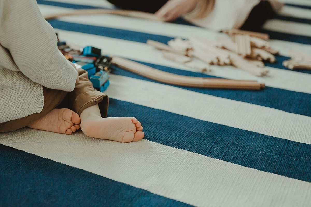 image of toddlers train set and feet while sitting on blue and white striped rug. photo by nyc family photographer krystil mcdowall