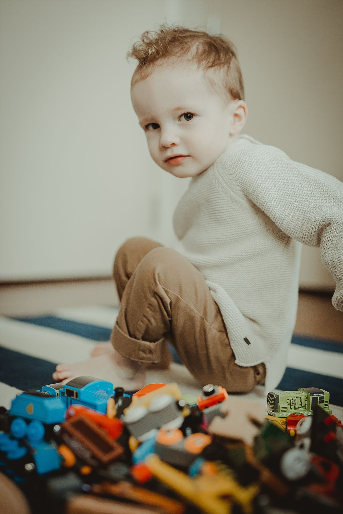 portrait of toddler in his room among a pile of toys. photographed by krystil mcdowall photography