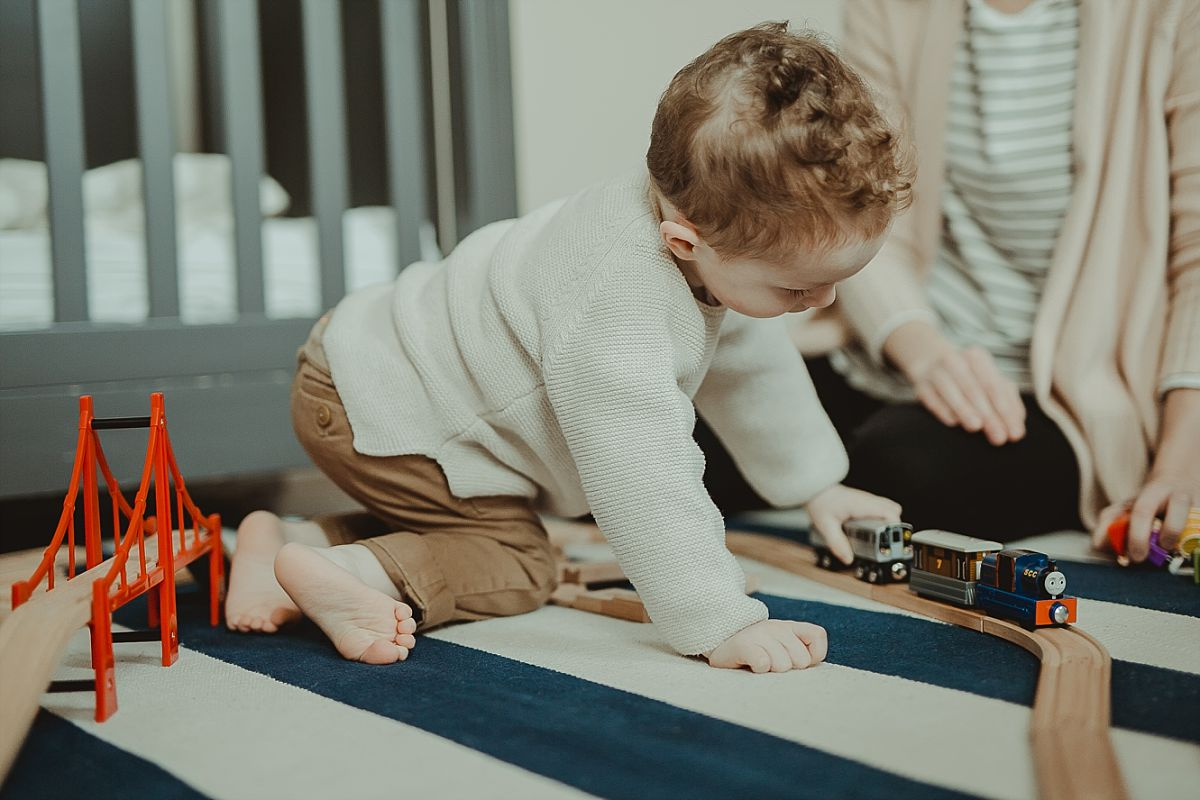candid photo of toddler playing with toy trucks in his room during documentary family session with nyc family photographer krystil mcdowall
