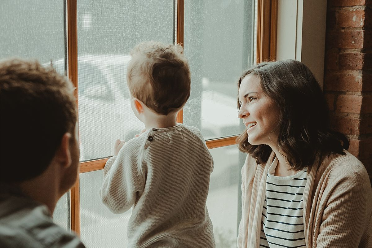 mom and son looking at cars and buses outside of big light filled window during in home family session. image by nyc family photographer krystil mcdowall