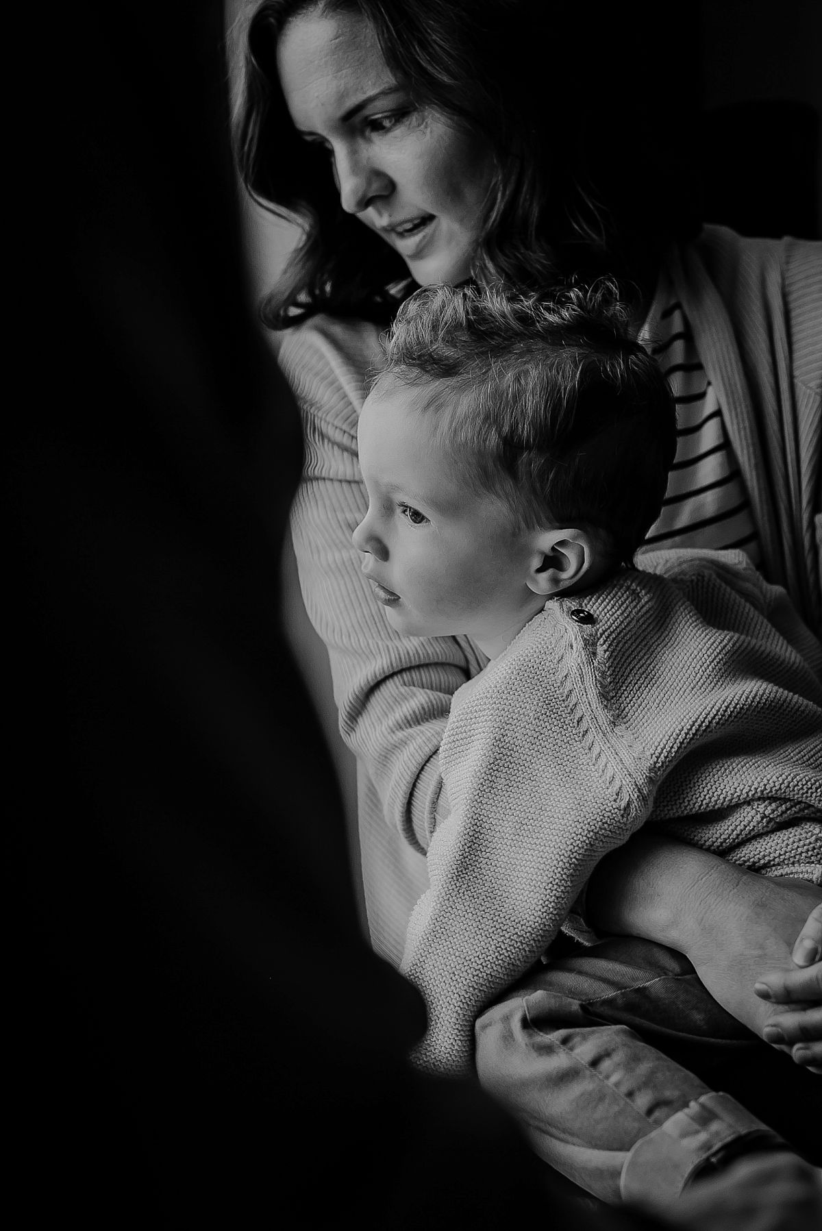 portrait of mom sitting on son's lap looking out of window. photographed by phtographer krystil mcdowall