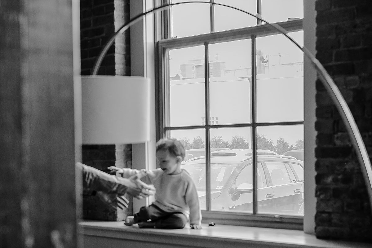 blurred image of son sitting in window and reaching out for dad. photo by nyc family photographer krystil mcdowall