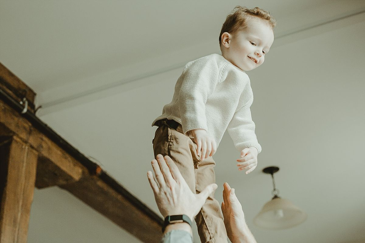 picture of son laughing as he's being thrown in the air by his dad during documentary family photo session
