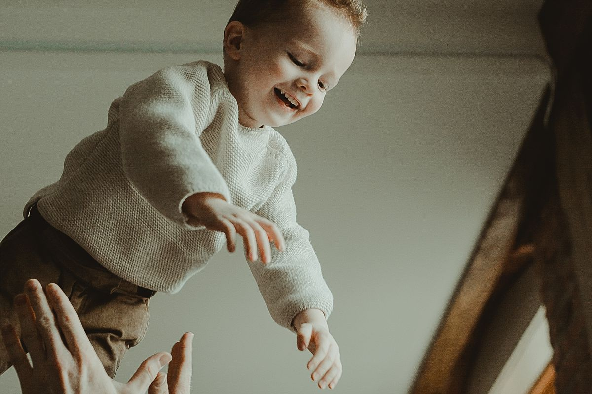 picture of son smiling as he's being thrown in the air by his dad during documentary family photo session. image by krystil mcdowall photography