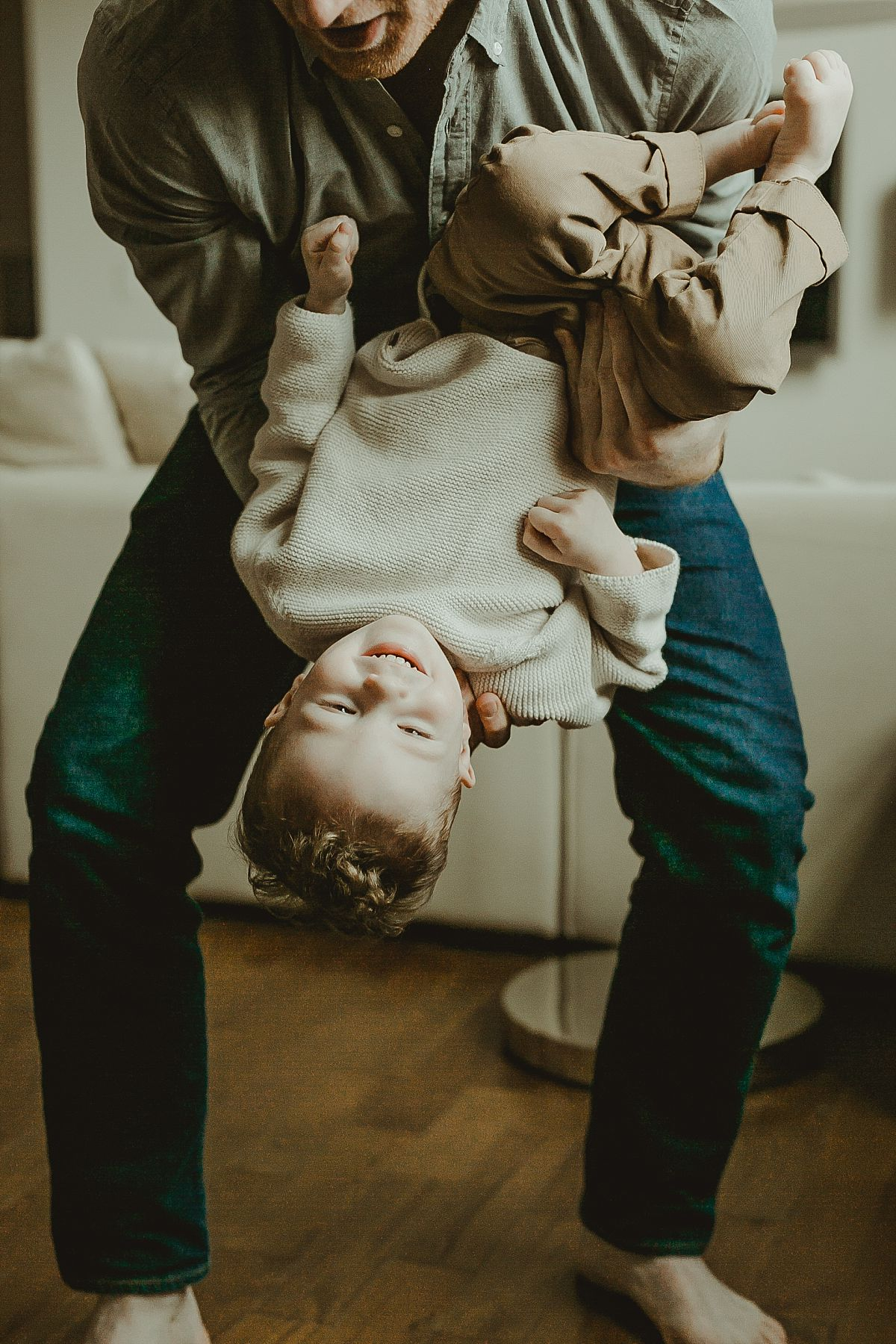 picture of dad holding son upside down while he is laughing during documentary family photo session. image by krystil mcdowall photography