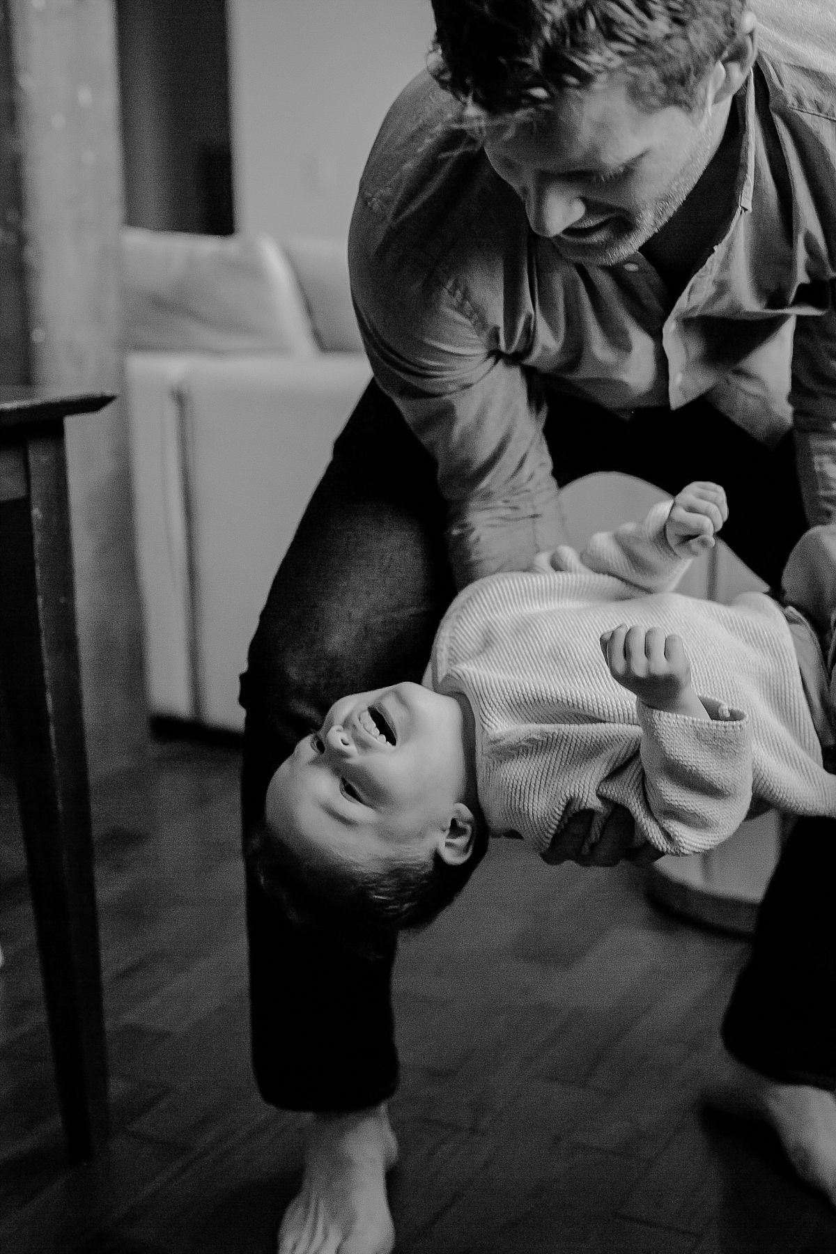 candid picture of dad holding son upside down while he is laughing. capturing real candid moments for your family during documentary family photo session. image by krystil mcdowall photography