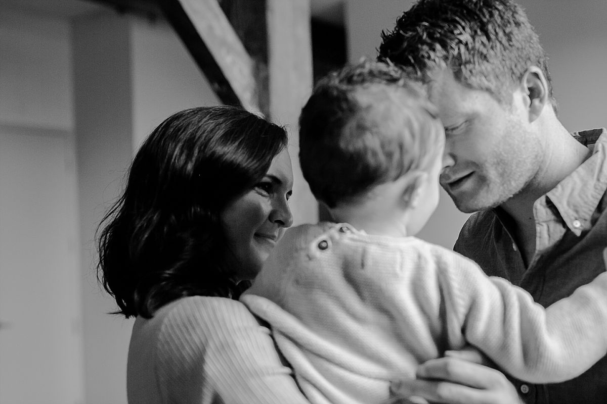 candid photo of mom and dad playing with son. image by nyc family photographer krystil mcdowall
