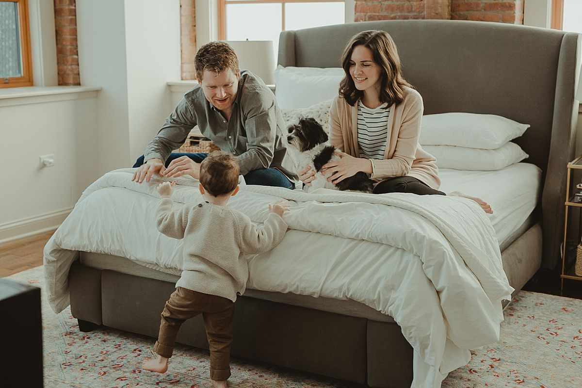 family portrait including dog as family plays in mom and dad's room. image by nyc family photographer krystil mcdowall