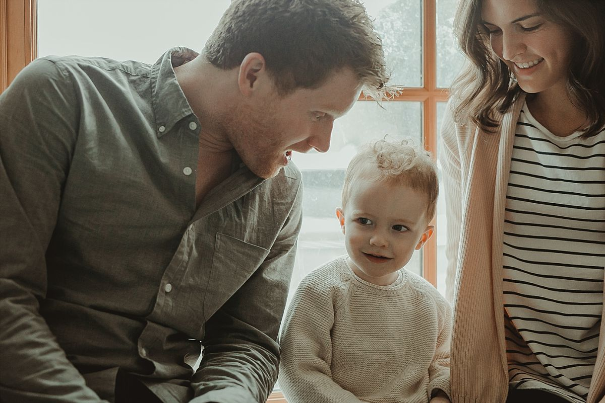 family smiling and hanging out together during in home family session. image by nyc family photographer krystil mcdowall