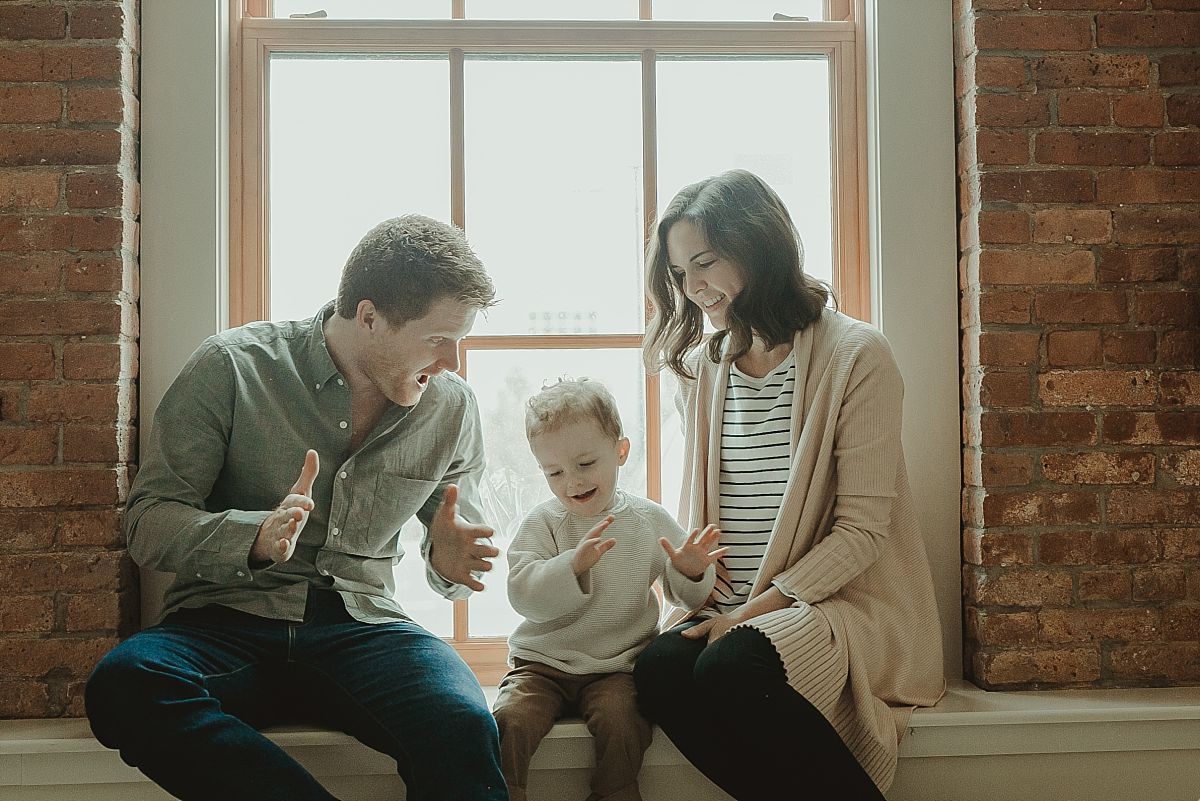 family sits in front of light filled window playing clapping hand games. krystil mcdowall ohotography capturing real candid family moments