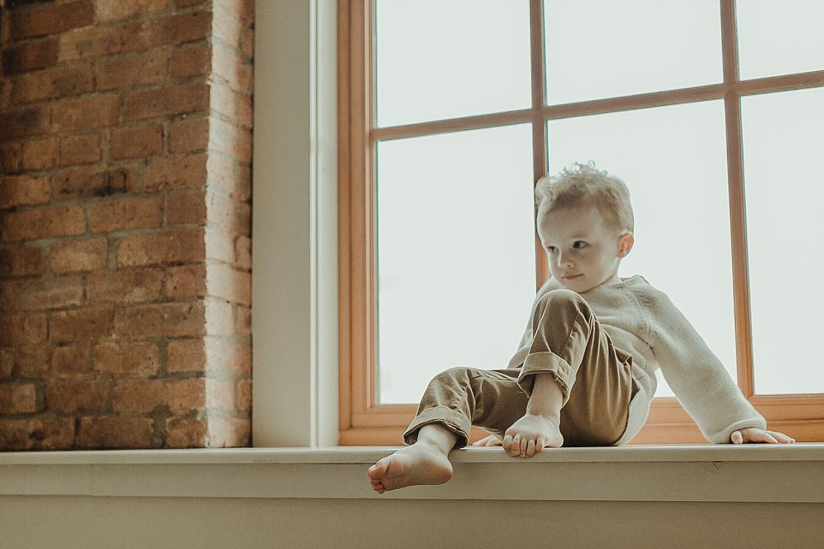 portrait of son sitting in light filled window. portrait by photographer krystil mcdowall