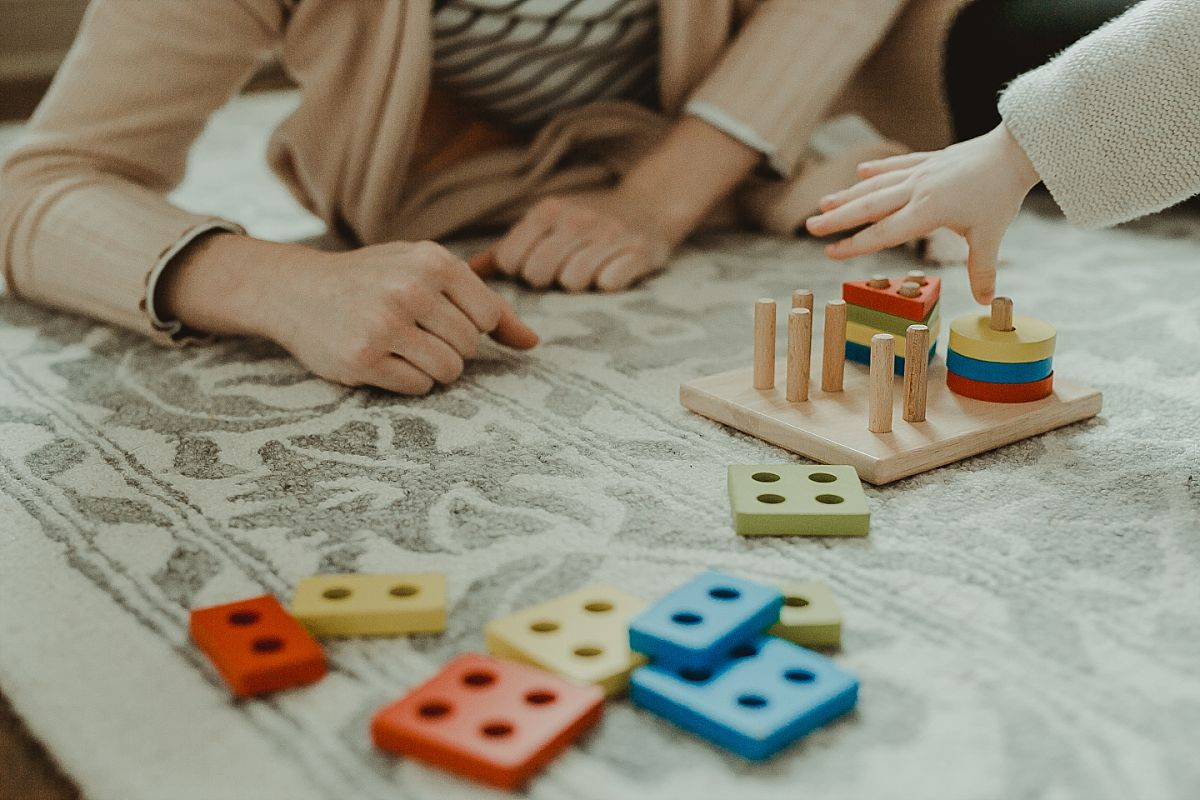photo of mom and son's hands and toddler plays with shape sorter toy