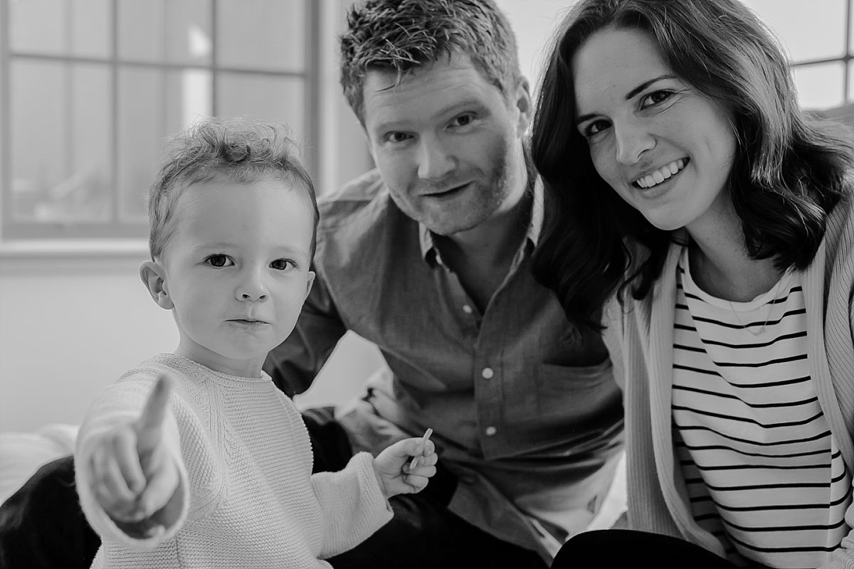 black and white family portrait from in home session taken while son eats candy. image by krystil mcdowall photography