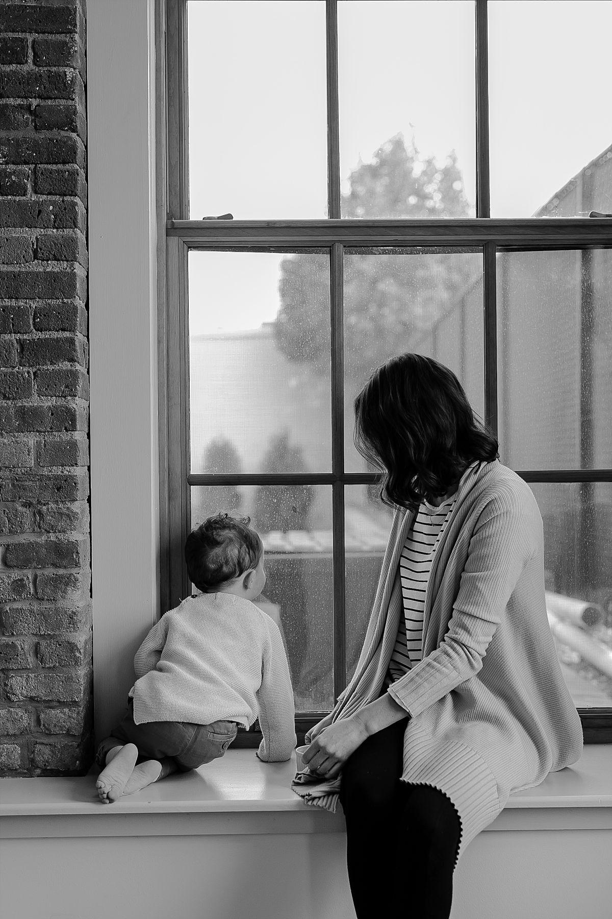 black and white image of mom and son looking out window to see train passing