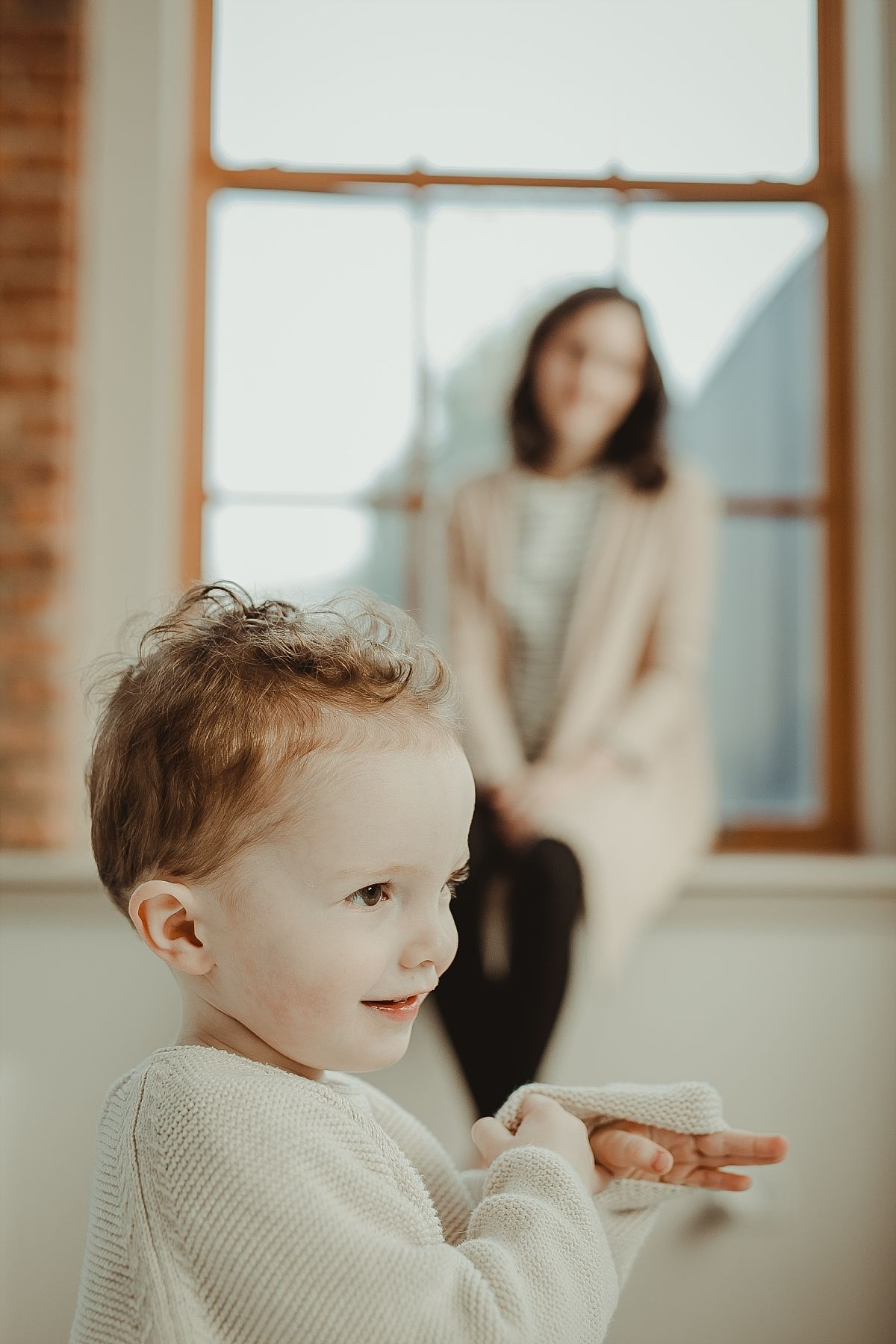 son looking at family dog with mom looking on with an adoring smile. capturing fun family images in your home