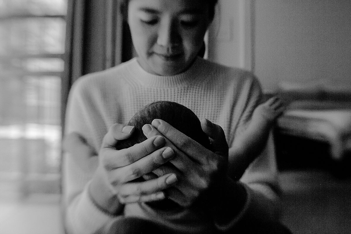 close up black and white photo of mom's hands as she holds newborn son in her arms. photo by krystil mcdowall photograhy
