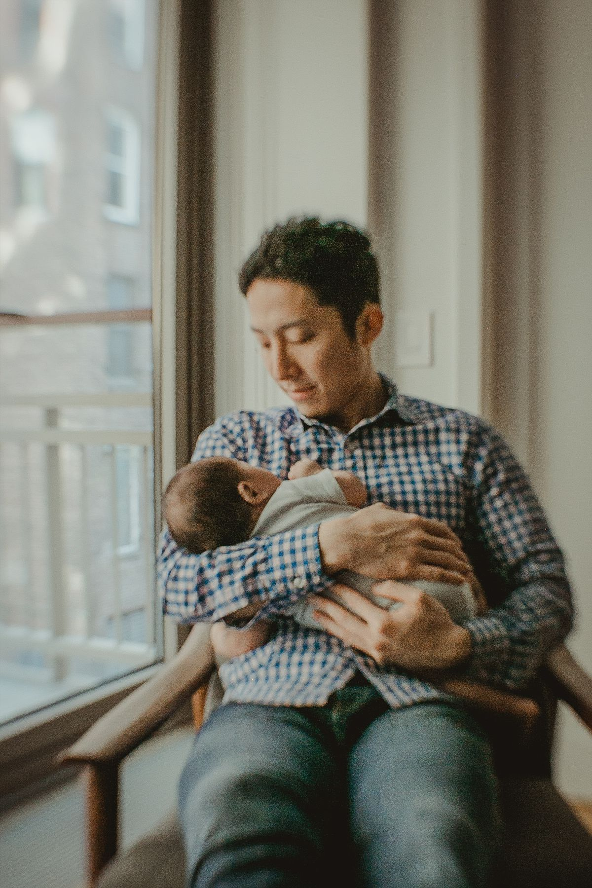 portrait of dad watching son sleep as he holds son in his arms. photo by nyc newborn photographer krystil mcdowall