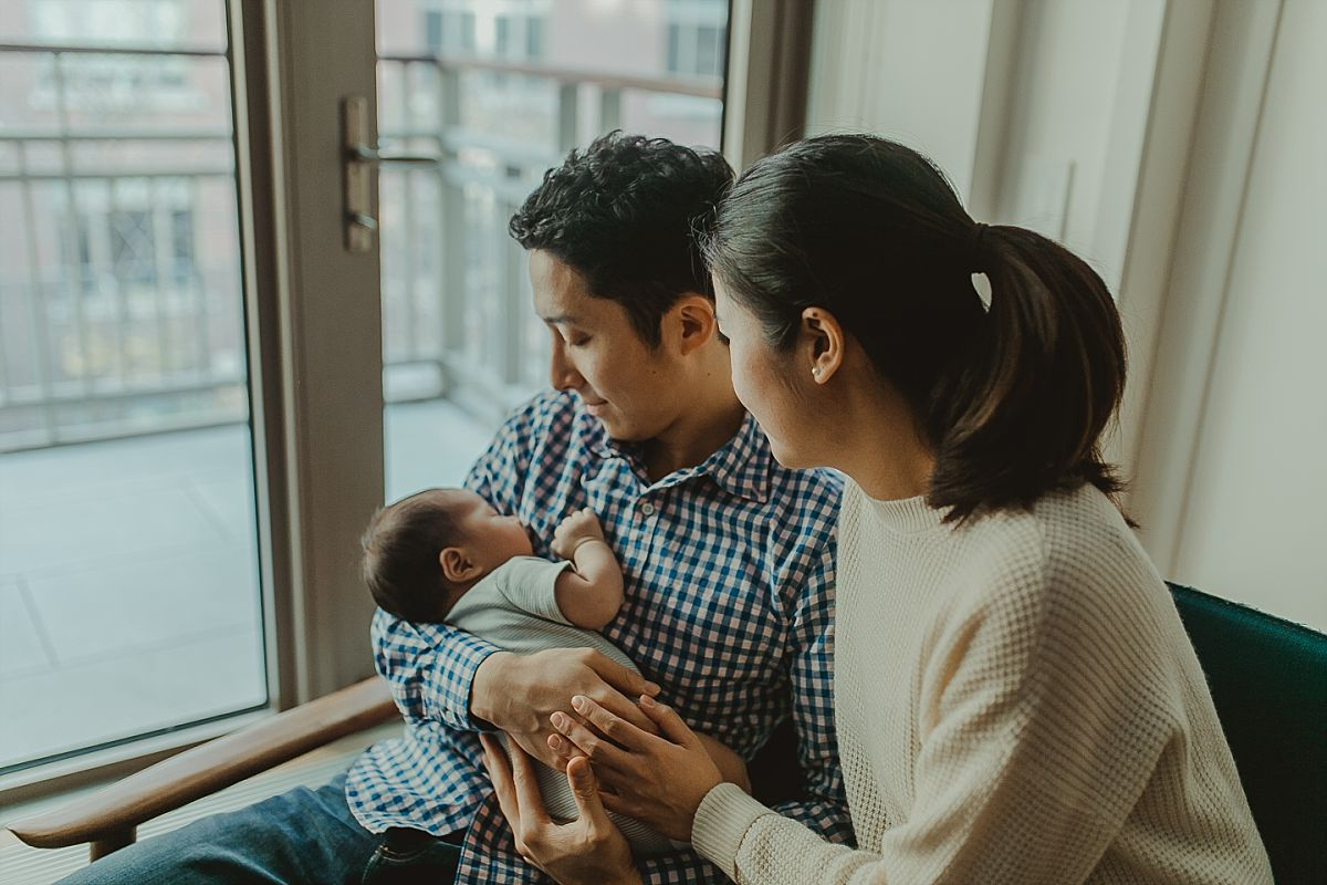 portrait of mom and dad watching newborn sleep in light filled living room of nyc home. photo by nyc newborn photographer krystil mcdowall