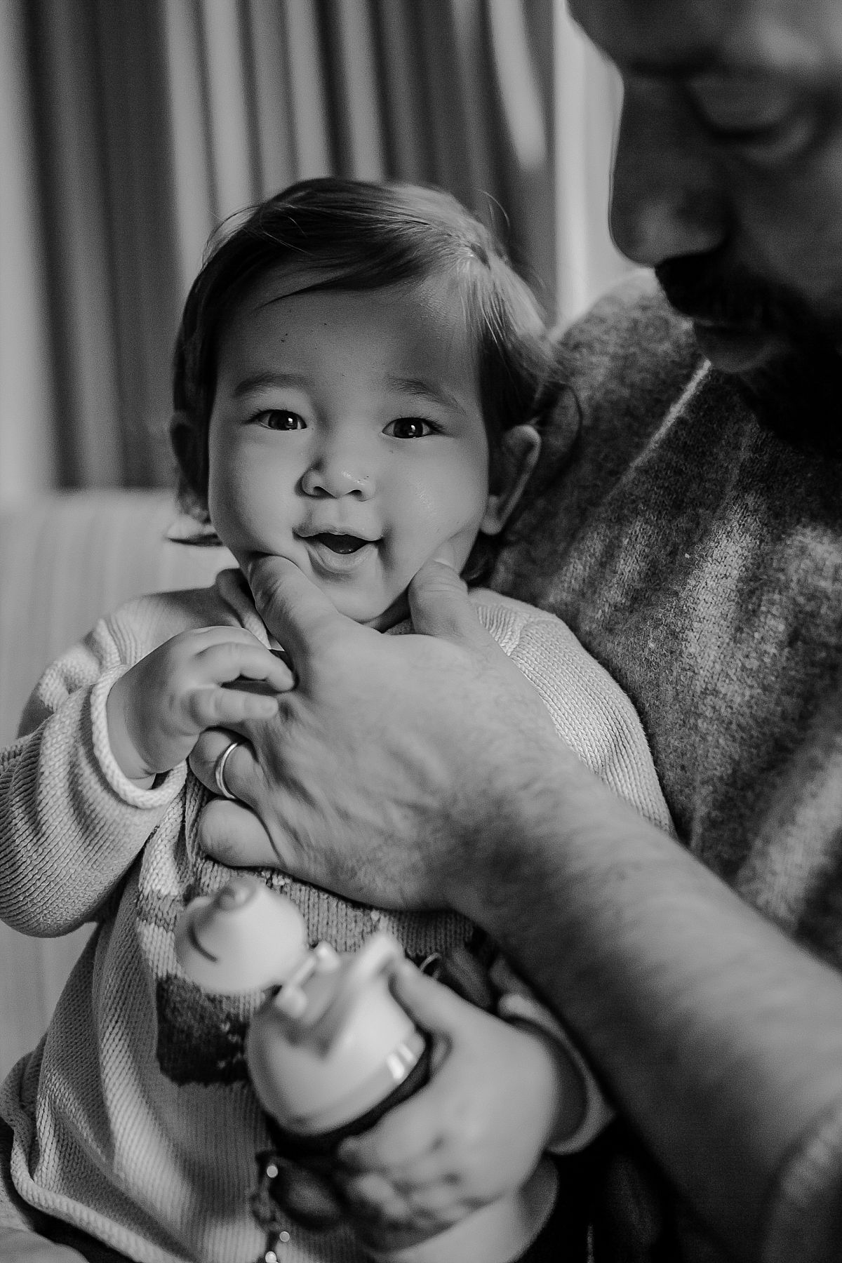 candid photo of dad squeezing daughter's cheeks while sitting on lap during family lifestyle photo session with Krystil McDowall photography