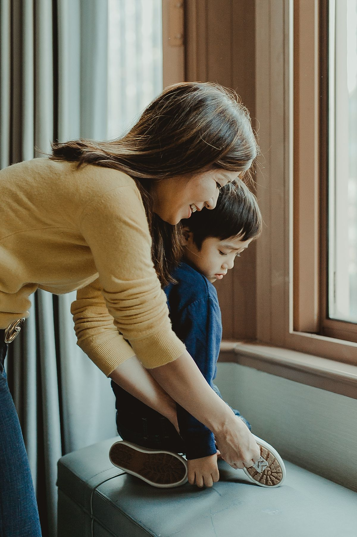 mom helping three year old son put on sneakers while looking out window of manhattan hotel. photograph by nyc family photographer krystil mcdowall